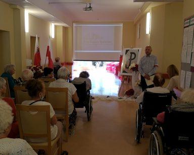 Kierownik Arkadiusz Wanat prowadzi spotkanie. Przed nim siedzą w rzędach seniorzy. Z tyłu ekran projektora. Na korytarzu polskie flagi.