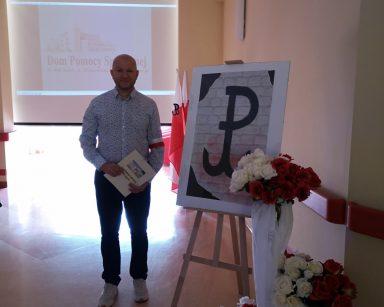 Kierownik Arkadiusz Wanat. Obok dekoracja. Plakat z symbolem Polski Walczącej, bukiety białych i czerwonych róż, białym tiul.