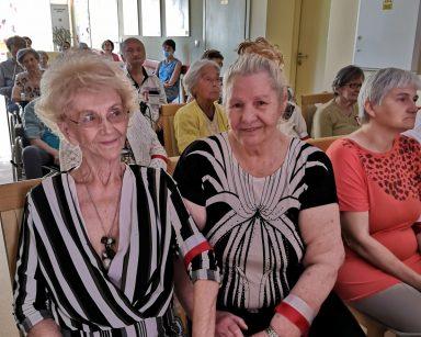 Seniorzy i pracownicy w trakcie spotkania. Siedzą w rzędach.