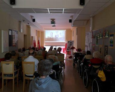 Seniorzy i pracownicy w trakcie spotkania. Siedzą w rzędach. Przed nimi ekran projektora z ujęciem Warszawy.