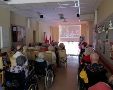 Seniorzy i pracownicy w trakcie spotkania. Siedzą w rzędach. Przed nimi ekran projektora z wyświetlanym filmem.