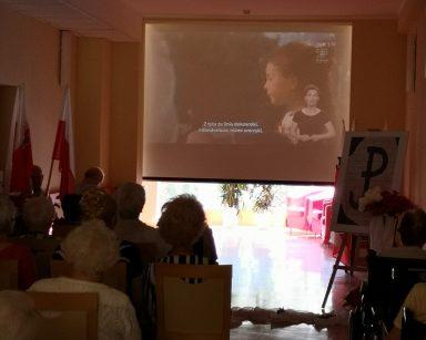 Ciemny korytarz. Seniorzy oglądają film na ekranie projektora. Przy ścianie polskie flagi, plakat z symbolem Polski Walczącej.