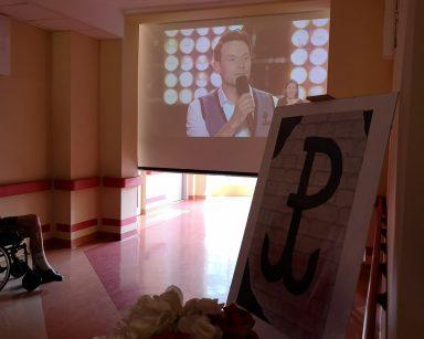 Ekran projektora. Na nim obraz mężczyzny z mikrofonem. Przy ścianie plakat z symbolem Polski Walczącej oraz bukiety białych i czerwonych róż.