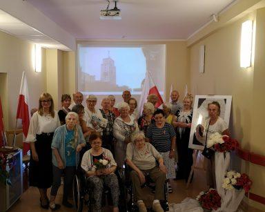 Dyrektorka Agnieszka Cysewska, pracownicy i seniorzy stoją w grupie. Z tyłu ekran projektora. Na korytarzu flagi, bukiety kwiatów.