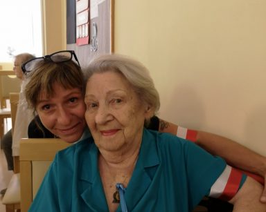 Kierowniczka Ewa Siłakiewicz-Witt przytula seniorkę. Uśmiechają się. Obie mają biało-czerwone opaski na ramieniu.