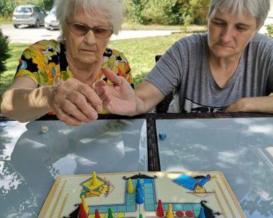 Zielony gród. Dwie seniorki siedzą w cieniu, przy stole. Przed nimi plansza do gry w chińczyka.