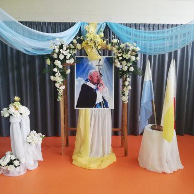 Jasna sala. Dekoracja z błękitnego, żółtego i białego materiału. Pergola z kwiatami. Portret Jana Pawła II na stelażu.