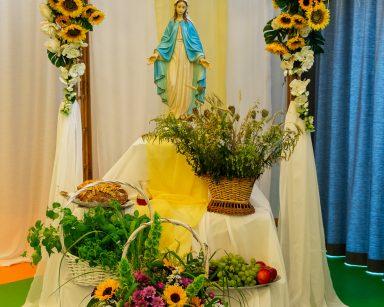 Pergola ozdobiona białymi i żółtymi kwiatami. Na podwyższeniu figurka Matki Boskiej. Poniżej kosze z darami do poświęcenia.