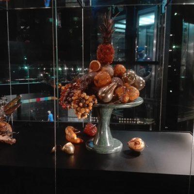 W szklanej gablocie owoce wykonane z bursztynu. Ananas, jabłka winogrona, gruszki, banany, cytrusy. Obok bursztynowy owad.