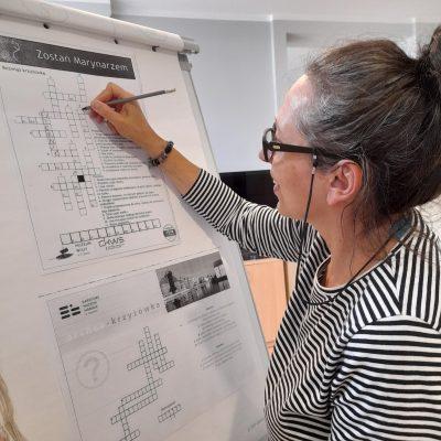 """Terapeutka Magdalena Poraj-Górska wpisuje hasło do krzyżówki na tablicy flipchart. U góry napis """"Zostań marynarzem""""."""