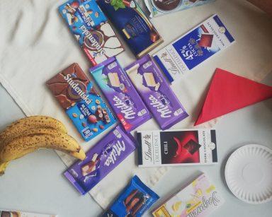 Na stole tabliczki czekolady w kolorowych opakowaniach. Obok czerwone serwetki, banany, papierowe talerzyki.