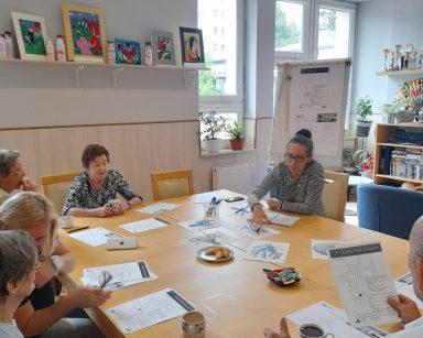 Przy stole terapeutka Magdalena Poraj-Górska i seniorzy. Na blacie krzyżówki, obrazki z morskimi stworzeniami, kubki z kawą.