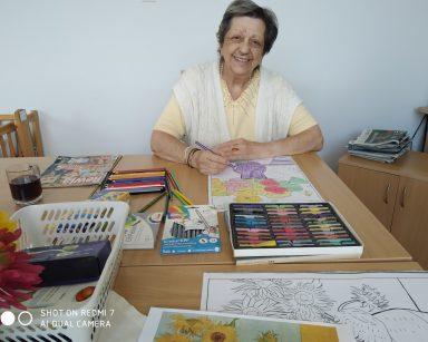 Seniorka przy stole koloruje obrazek. Uśmiecha się. Na blacie obrazki do kolorowania, kredki, pastele, kubek z kawą.