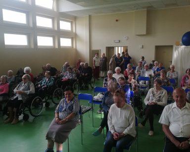 Sala. Seniorzy i pracownicy wchodzą przez drzwi. Część już siedzi w rzędach i czeka na koncert.