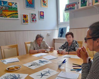 Przy stole terapeutka Magdalena Poraj-Górska i seniorki. Na blacie krzyżówki, obrazki z morskimi stworzeniami, kubki z kawą.
