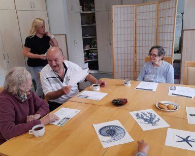 Przy stole seniorzy. Śmieją się i rozmawiają. Na blacie krzyżówki, obrazki z morskimi stworzeniami, kubki z kawą, ciastka.