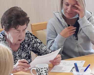 Przy stole kierowniczka Ilona Gajewska i seniorka. Zastanawiają się nad hasłem w krzyżówce.
