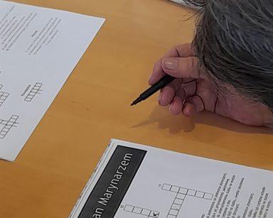 Seniorka pochyla się nad krzyżówką z napisem