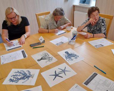Przy stole neurologopedka Ania Szmaja-Wysocka i seniorki. Rozwiązują krzyżówki. Na blacie krzyżówki, obrazki i kubki z kawą.