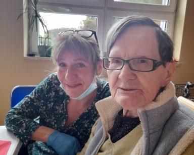 Przy stole siedzą kierowniczka Ewa Siłakiewicz-Witt i seniorka. Uśmiechają się.
