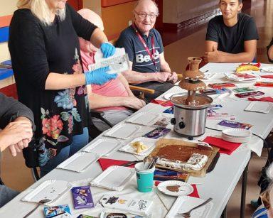 Neurologopedka Ania Szmaja-Wysocka rozpakowuje czekoladę. Przy stole siedzą seniorzy i pracownicy. Na blacie różne czekolady.