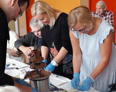 Przy stole pracownicy i seniorzy. Na blacie tabliczki czekolady w kolorowych opakowaniach, fontanna z płynną czekoladą.
