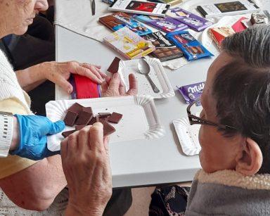 Seniorzy przy stole. Na blacie różne rodzaje czekolad w kolorowych opakowaniach. Seniorka częstuje się kawałkiem czekolady.