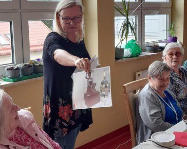 Przy stole seniorzy. Neurologopedka Ania Szmaja-Wysocka pokazuje zdjęcie syrenki z czekolady. Na blacie różne czekolady.