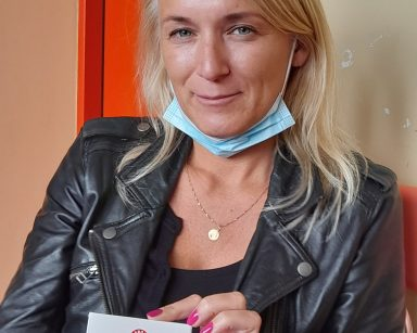 Kierowniczka Ilona Gajewska trzyma w dłoniach czekoladę w kolorowym opakowaniu. Uśmiecha się.