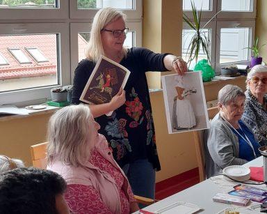 Przy stole seniorzy. Neurologopedka Ania Szmaja-Wysocka prowadzi zajęcia. Pokazuje zdjęcia. Na blacie różne czekolady.