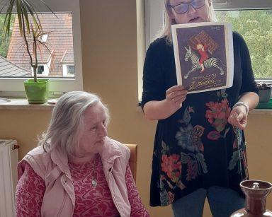 Neurologopedka Ania Szmaja-Wysocka pokazuje seniorom plakat z chłopcem na zebrze i tabliczkami czekolady na placach.