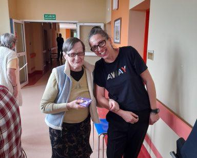 Na korytarzu seniorka i terapeutka Magdalena Poraj-Górska. Uśmiechają się. Seniorka ma w dłoniach tabliczkę czekolady.
