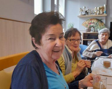 Trzy seniorki przy stole. Śmieją się. Przed nimi na blacie kubki z kawą.