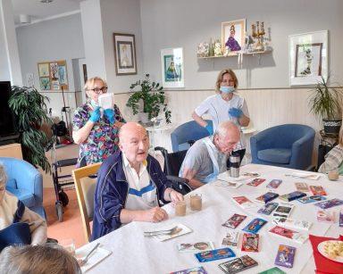Seniorzy przy stole. Na stole czekolady, kawa, papierowe talerzyki. Z tyłu opiekunki Katarzyna Weier i Małgorzata Kuświk.