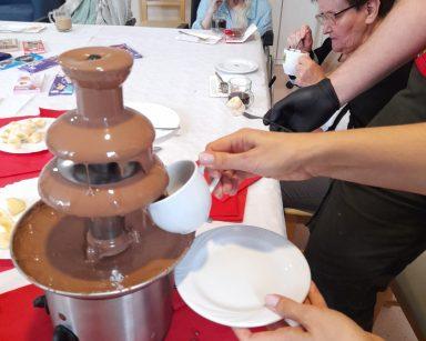 Pracownik napełnia kubek płynną czekoladą z fontanny. Przy stole seniorzy. Siedzą przy kawie, jedzą słodycze.