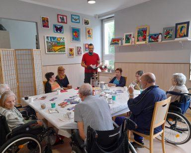 Administrator Łukasz Cielebański prowadzi zajęcia. Przy stole pracownicy i seniorzy. Na blacie kubki z kawą, słodycze.
