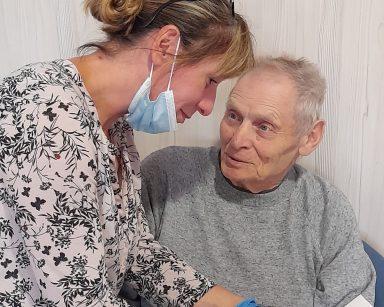 Kierowniczka Ewa Siłakiewicz-Witt nachyla się nad seniorem. W dłoniach trzyma tabliczkę czekolady. Senior uśmiecha się.
