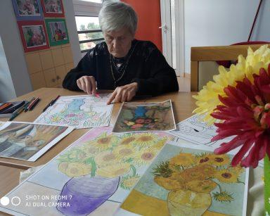 Seniorka koloruje obrazek według wzoru. Na blacie kredki, obrazy i obrazki do kolorowania.