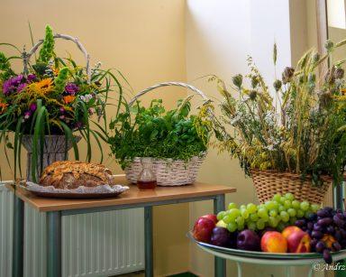 Dary do poświęcenia. Kosze z kwiatami i ziołami, wino w karafce, na tacach chleb i owoce.