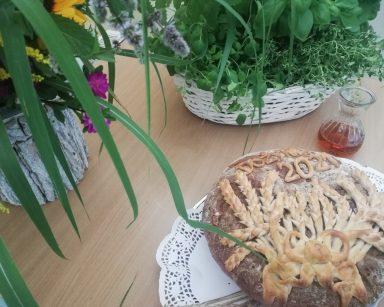 Na blacie kosze z kwiatami i ziołami, szklana karafka z winem, chleb ozdobiony kłosami.