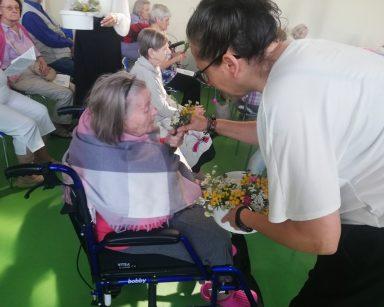 Na sali seniorzy siedzą w rzędach. Terapeutka Magdalena Poraj-Górska i inni pracownicy rozdają im bukieciki z ziół i kwiatów.