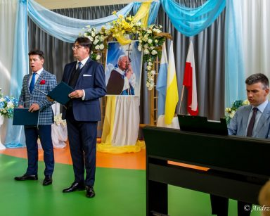 Artyści Dariusz Wójcik i Jacek Szymański stoją na środku. Przy pianinie Paweł Zawada. W tle dekoracja, portret Jana Pawła II.