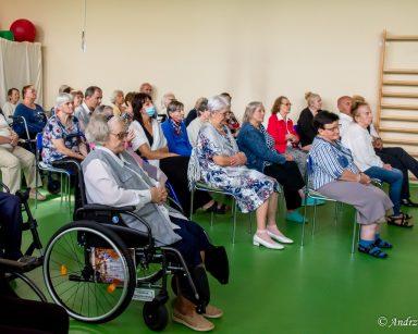 Seniorzy, wolontariusze i pracownicy siedzą w rzędach na sali. Oglądają koncert.