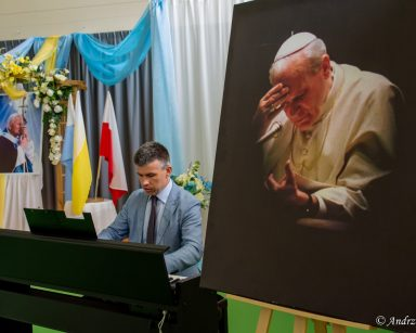 Przy portrecie papieża Paweł Zawada gra na pianinie. Za nim dekoracja z kwiatów i portret Jana Pawła II z krzyżem.