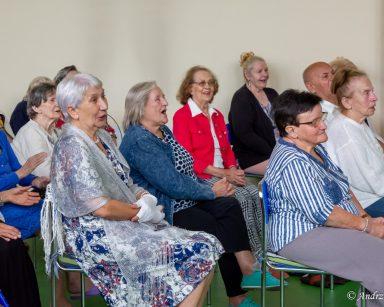 Jasna sala. Seniorzy siedzą w rzędach. Część z nich śmieje się i śpiewa.