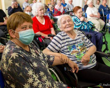 Jasna sala. Seniorzy, wolontariusze i pracownicy siedzą w rzędach. Część z nich śmieje się i śpiewa.