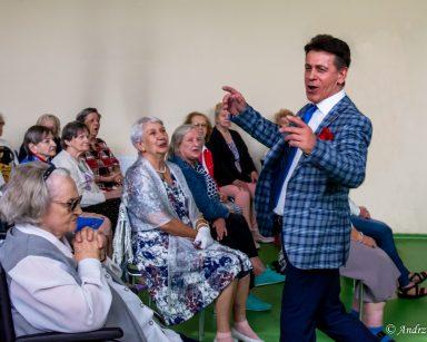 Artysta Dariusz Wójcik śpiewa i gestykuluje. Przed nim siedzą seniorki. Patrzą na niego, część z nich się śmieje