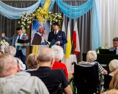 Artyści Dariusz Wójcik i Jacek Szymański Paweł Zawada przed dekoracją z kwiatów i portretem papieża. Przed nimi seniorzy.