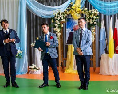 Artyści Dariusz Wójcik i Jacek Szymański i Paweł Zawada stoją na środku. W tle dekoracja z kwiatów, portret Jana Pawła II.