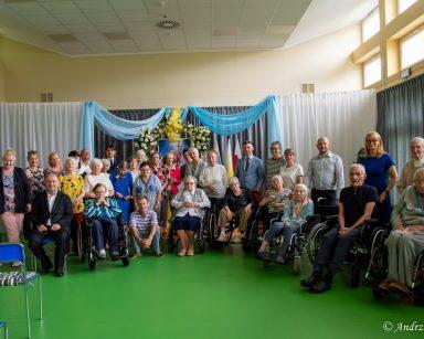 Zdjęcie grupowe. Sala udekorowana na koncert. Dyrektorka Agnieszka Cysewska, seniorzy, artyści, wolontariusze i pracownicy.